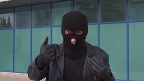 Misdadige mensendief of rover die in masker iemand uitnodigen stock footage