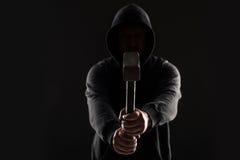 Misdadiger in donkere kleren en balaclava met hamer stock afbeelding