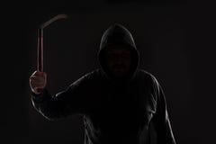 Misdadiger in donkere kleren en balaclava met zeis royalty-vrije stock foto