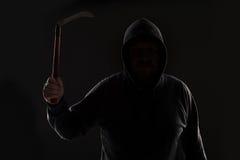 Misdadiger in donkere kleren en balaclava met zeis stock foto