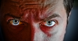 Misdadiger met bloed op zijn gezicht stock afbeeldingen
