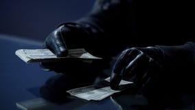 Misdadiger in zwarte handschoenen die bundel van geld tellen die voor het begaan van misdaad wordt verdiend stock fotografie