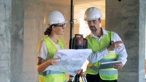 Mise à niveau du dispositif et deux spécialistes en construction, les constructeurs, les constructeurs se tenant près de lui et p banque de vidéos