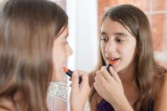 Mise de l'adolescence hispanique sur le rouge à lèvres devant un miroir Photo stock