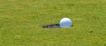 Mise de la bille de golf dans le trou photographie stock libre de droits