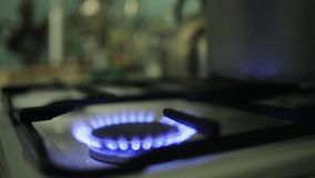 Mise de la casserole en aluminium énorme sur la cuisinière à gaz brûlante Incendie bleu banque de vidéos