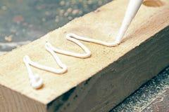 Mise de la colle sur un morceau de bois images libres de droits
