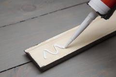 Mise de la colle sur un morceau de plinthe en bois photo libre de droits