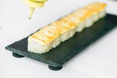 Mise de la sauce sur le petit pain de sushi japonais non coupé Photo libre de droits