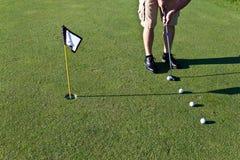 Mise de pratique de golfeur avec plusieurs boules de golf Image libre de droits