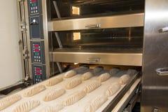 Mise du pain cuit au four frais dans le support Processus de fabrication de pain espagnol Photo libre de droits