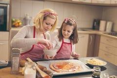 Mise du salami sur la pâte de pizza Photos stock