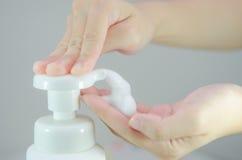 Mise du savon de mousse de fouet sur la main Photos stock