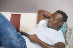 Mise en réseau afro-américaine noire réussie attrayante et heureuse d'homme avec l'ordinateur portable au sourire de divan de sal images libres de droits