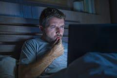 Mise en réseau attrayante et décontractée d'homme d'intoxiqué d'Internet concentrée tard la nuit sur le lit avec l'ordinateur por images stock