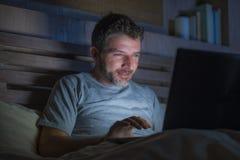 Mise en réseau attrayante et décontractée d'homme d'intoxiqué d'Internet concentrée tard la nuit sur le lit avec l'ordinateur por images libres de droits