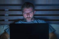 Mise en réseau attrayante et décontractée d'homme d'intoxiqué d'Internet concentrée tard la nuit sur le lit avec l'ordinateur por photos libres de droits