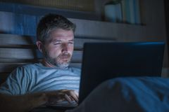 Mise en réseau attrayante et décontractée d'homme d'intoxiqué d'Internet concentrée tard la nuit sur le lit avec l'ordinateur por image stock