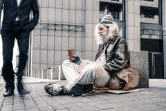 Miserabele grijs-haired oude daklozen die motionlessly op koude grond zitten royalty-vrije stock foto