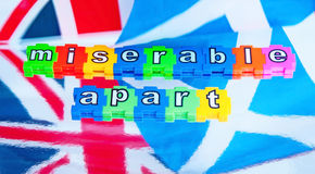 Miserable apart. Scottish and British flags  with the words  miserable apart   in colorful jigsaw style lower case letters , relating to the outcome of the Royalty Free Stock Image
