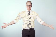 Miserable businessman covered by blank yellow stickers. Royalty Free Stock Photos