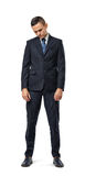 Miserable businessman full-height looking down isolated on the white background. Stock Photo