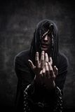 Miserable cultist. Portrait of miserable chained young man in hood Stock Images