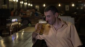Miserable depressed man having a beer alone at the bar in a pub -. Miserable depressed man having a beer alone at the bar in a pub stock video footage