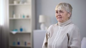 Miserable elderly lady sitting alone in nursing house and crying, depression. Stock photo stock images
