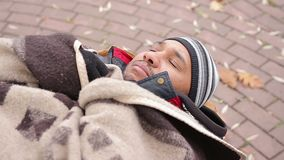 Miserable face of homeless man sleeping on bench, feeling cold and unhappy. Stock footage stock video