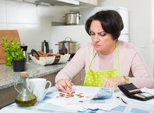 Miserable female counting money for payment. Depressed broke woman without enough money to pay bills Royalty Free Stock Image