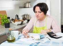 Miserable female counting money for payment Stock Image