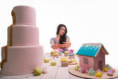 Miserable girl because of refusal. From delicious bakery. Variety of sweets on white wooden table on pastel pink background. Colofrul gingerbread house, big stock image