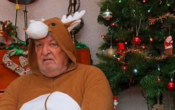 Miserable grumpy old man at Christmas. A miserable grumpy senior man dressed in a reindeer suit at Christmas time. Sitting by a Christmas tree looking very Royalty Free Stock Photos