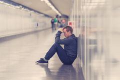 Miserable jobless young man crying Drug addict Homeless in depression stress sitting on ground street subway tunnel looking. Desperate leaning on wall alone in stock image