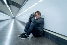 Miserable jobless young man crying Drug addict Homeless in depression stress sitting on ground street subway tunnel looking. Desperate leaning on wall alone in stock photography