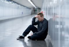 Miserable jobless young man crying Drug addict Homeless in depression stress sitting on ground street subway tunnel looking. Desperate leaning on wall alone in stock images