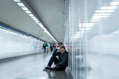 Miserable jobless young man crying Drug addict Homeless in depression stress sitting on ground street subway tunnel looking. Desperate leaning on wall alone in royalty free stock photos