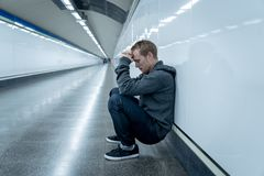 Miserable jobless young man crying Drug addict Homeless in depression stress sitting on ground street subway tunnel looking. Desperate leaning on wall alone in royalty free stock images