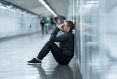 Miserable jobless young man crying Drug addict Homeless in depression stress sitting on ground street subway tunnel looking. Desperate leaning on wall alone in royalty free stock photo