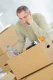 Miserable man with belongings in cardboard boxes. Miserable man with his belongings in cardboard boxes stock images