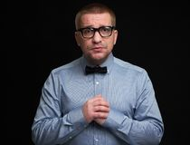 Miserable man wearing glasses and bow tie. On black background. Trendy guy looking at camera. People emotions concept stock image