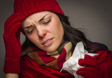 Miserable Mixed Race Woman Blowing Her Sore Nose with Tissue Stock Photography