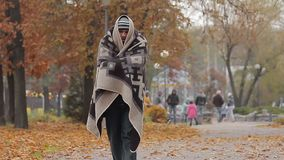 Miserable poor man walking in city park covered from cold with shabby blanket. Stock footage stock video footage
