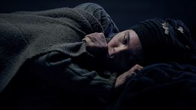 Miserable refugee covered by blanket lying on street and crying, missing home. Stock photo royalty free stock images