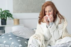 Miserable woman blowing runny nose. Miserable woman sitting on the bed wrapped in blanket, feeling sick with flu, having fever and blowing runny nose with stock images