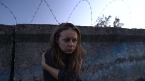 Miserable woman sitting near barb wire, drug addicted in correctional facility. Stock footage stock footage