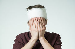 Man with bandage on his head. Miserable young guy with bandage on his head closing face by hands. Image related with treatment of the wounds Stock Photo
