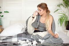 Miserable young woman sitting on the bed wrapped in warm blanket feeling sick with flu.  royalty free stock image