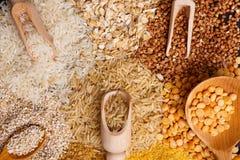 Miserables ed i cucchiai hanno riempito di cereali sui precedenti di un mucchio dei cereali Vista da sopra Fotografia Stock